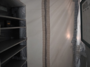 image of plastic wrapped shelves and zippered doorway to cleanroom